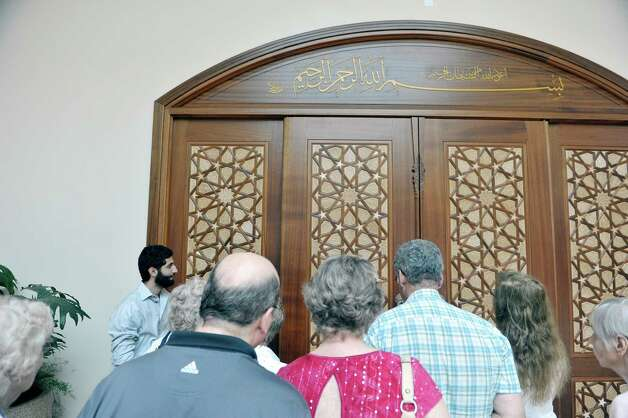Visitors look over the doors to the prayer hall as Ahmad Abu-Hakmeh, background left, gives a tour during an open house at the Al-Hidaya Center on Sunday, May 10, 2015, in Latham, N.Y.  The mosque can hold more than 800 worshipers and in keeping with Muslim tradition, there is no mortgage on the property and no loans were taken out. Planning and fundraising took 25 years. (Paul Buckowski / Times Union) Photo: PAUL BUCKOWSKI / 00031649A