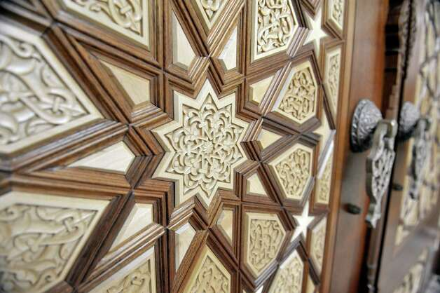 A view of the wood design of the doors to the prayer hall  during an open house at the Al-Hidaya Center on Sunday, May 10, 2015, in Latham, N.Y.  The wood doors and the ornate pieces all came from Turkey and the pieces of the door are floating, where they are pieced together without the use of glue or nails.  There are 99 pieces to the doors with symbolizes the 99 names of God.  The mosque can hold more than 800 worshipers and in keeping with Muslim tradition, there is no mortgage on the property and no loans were taken out. Planning and fundraising took 25 years. (Paul Buckowski / Times Union) Photo: PAUL BUCKOWSKI / 00031649A