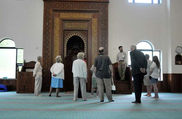 Mehmet Demiroglu, fourth from right, former president of the board of directors of the Al-Hidaya Center and project manager for the building of the center, gives a tour of the prayer hall to visitors  during an open house at the Al-Hidaya Center on Sunday, May 10, 2015, in Latham, N.Y.  (Paul Buckowski / Times Union) Photo: PAUL BUCKOWSKI / 00031649A
