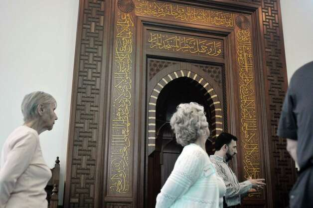 Mehmet Demiroglu, right, former president of the board of directors of the Al-Hidaya Center and project manager for the building of the center, gives a tour of the prayer hall to visitors  during an open house at the Al-Hidaya Center on Sunday, May 10, 2015, in Latham, N.Y.  (Paul Buckowski / Times Union) Photo: PAUL BUCKOWSKI / 00031649A