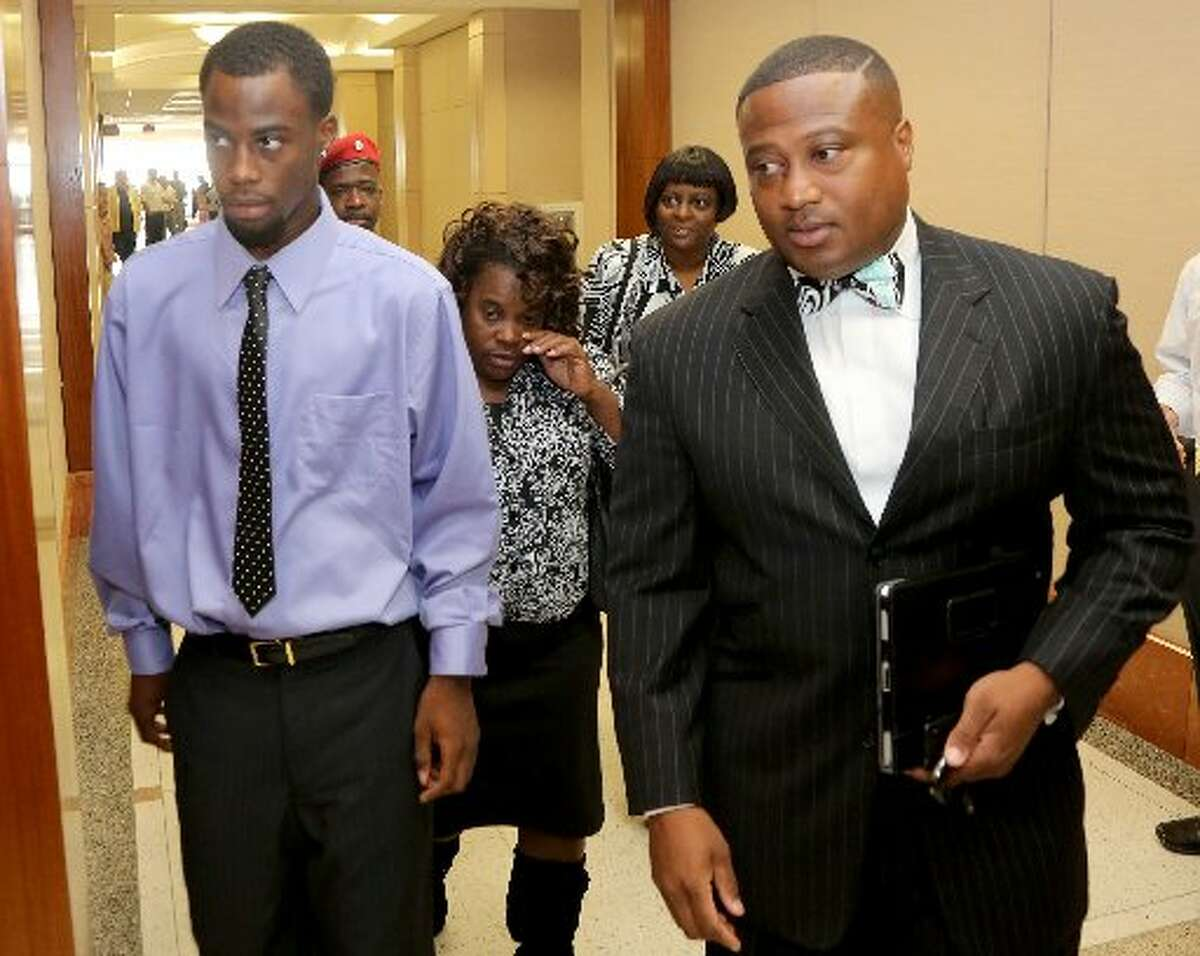 Chad Holley, with his mother Joyce Holley and Quanell X enters the 178th court in Houston in 2012. (Thomas B. Shea / For the Chronicle )
