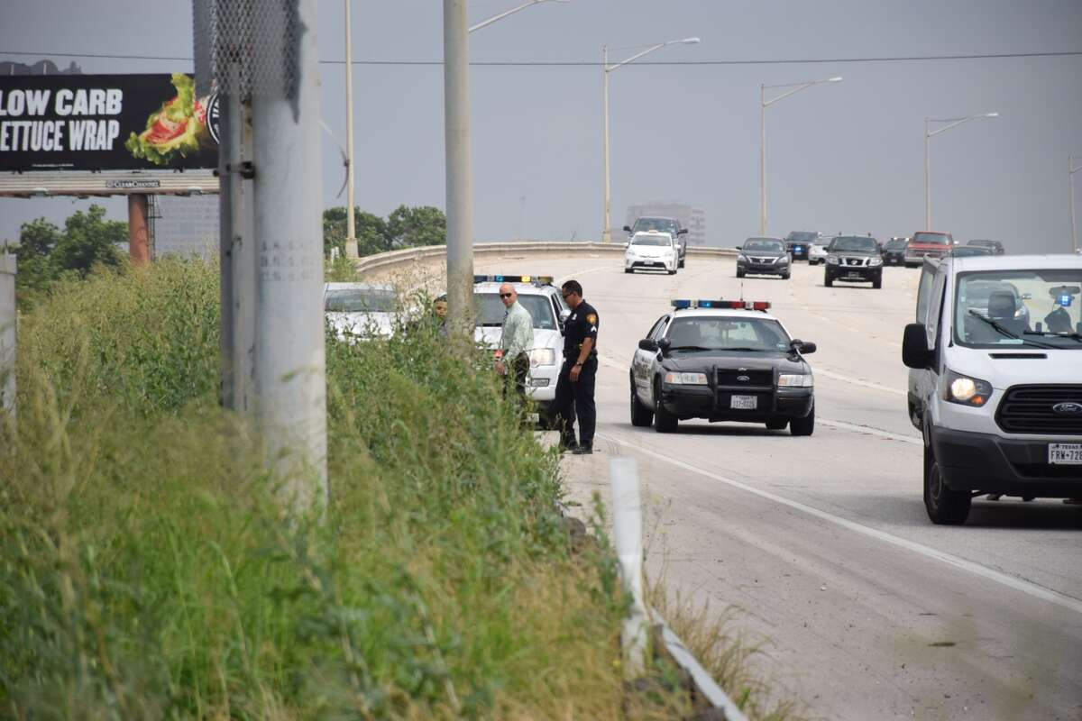 San Antonio police officers investigate the body of a baby found on the side of Interstate 37 south of downtown San Antonio on May 11, 2015.