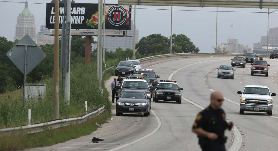 San Antonio police investigate a scene on the side of IH-37 near IH-10 where a deceased small baby  was found inside of a piece of luggage about 10:30 a.m. Monday May 11, 2015.. Police spokesman Javier Salazar said a worker who was about to mow the area did an inspection of the area before mowing and opened the piece of luggage and contacted police. Photo: John Davenport, San Antonio Express-News / ©San Antonio Express-News/John Davenport