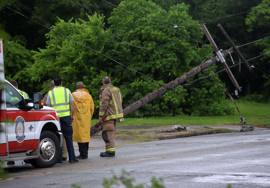 Emergency workers wait for repair crews on Beaumont's Magnolia Street Monday after a woman driving an SUV struck the police knocking it down. Photo taken Monday, May 11, 2015 Guiseppe Barranco/The Enterprise Photo: Guiseppe Barranco, Photo Editor