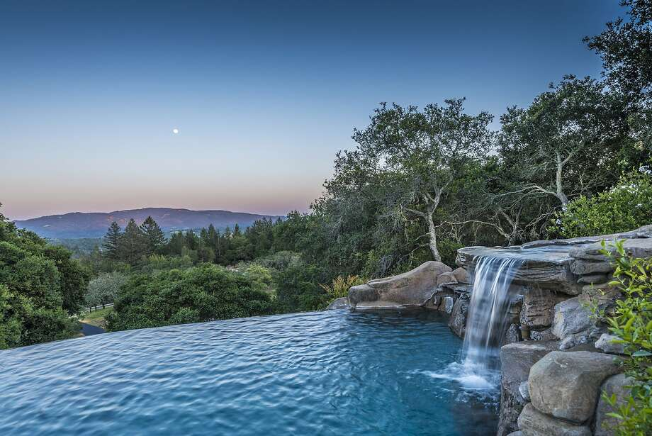 A waterfall fills an infinity edge pool overlooking the landscape. Photo: Photography By OpenHomesPhotogra