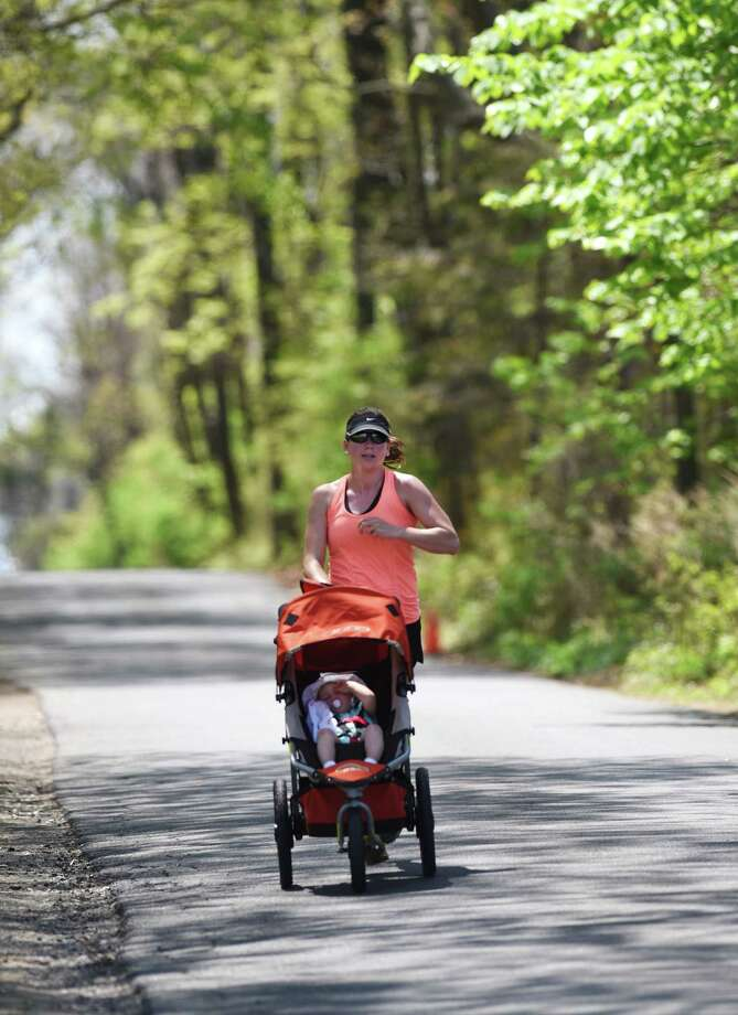 Sarah Sippel, of Old Greenwich, goes for a run while pushing a stroller with her daughter, Ella Sippel, through Greewich Point Park in Old Greenwich, Conn.  Photo: Tyler Sizemore / Greenwich Time