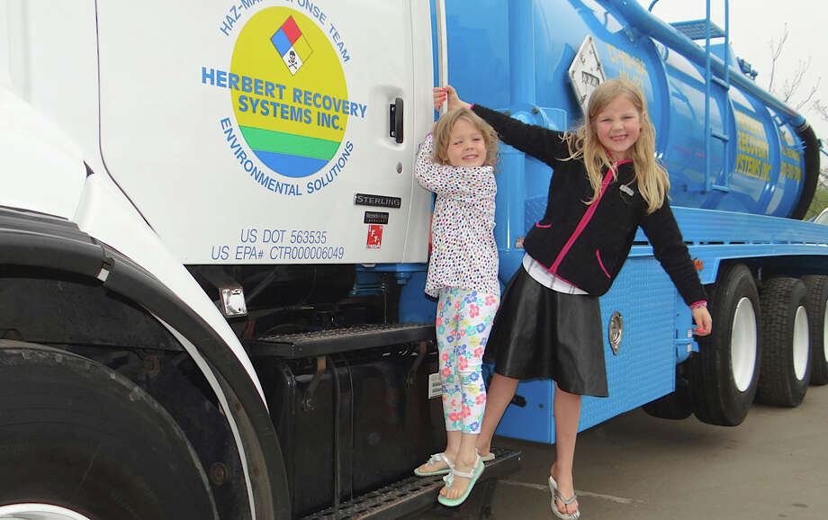 Kate Bulkeley, 6, and sister, Sutton get the hang of things off Herbert Recovery System's Haz-Mat truck at St. Paul Christian School's Touch-A-Truck event. Photo: Mike Lauterborn / Westport News