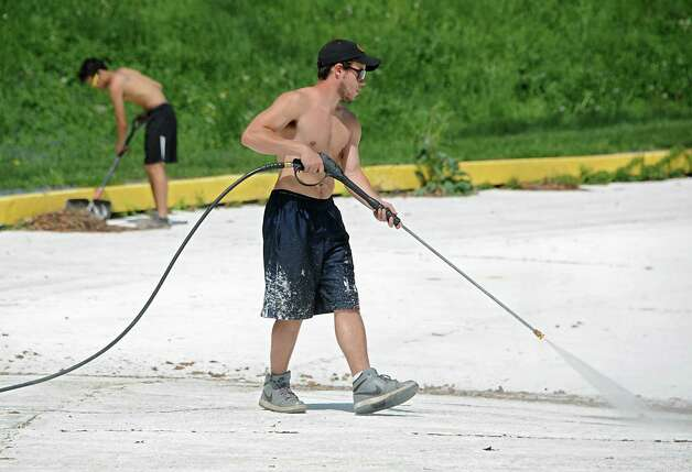 Department of Recreation employees Matt Campbell, left, and Joe Teti, both of Albany, clean up the public pool in Lincoln Park on Monday, May 11, 2015 in Albany, N.Y. (Lori Van Buren / Times Union) Photo: Lori Van Buren