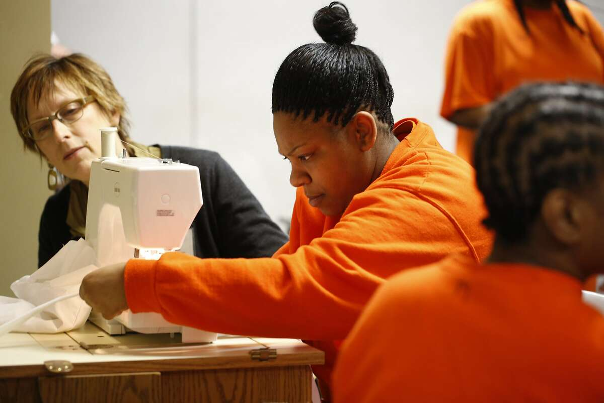 San Francisco State University professor of Apparel Design and Merchandising Connie Ulasewicz goes of the finishing touches on a project with San Francisco County jail inmate Johnetta Dixon on Monday May 11, 2015 in San Francisco, Calif. Dixon finished six weeks of sewing instruction at the county jail and hopes to use her new skills in the future.
