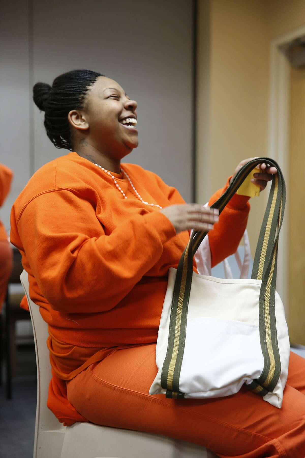 After finishing six weeks of sewing instruction at the San Francisco County Jail, inmate Johnetta Dixon shows off one of her creations on the last day of class on Monday May 11, 2015 in San Francisco, Calif. Dixon finished six weeks of sewing instruction at the county jail and hopes to use her new skills in the future.