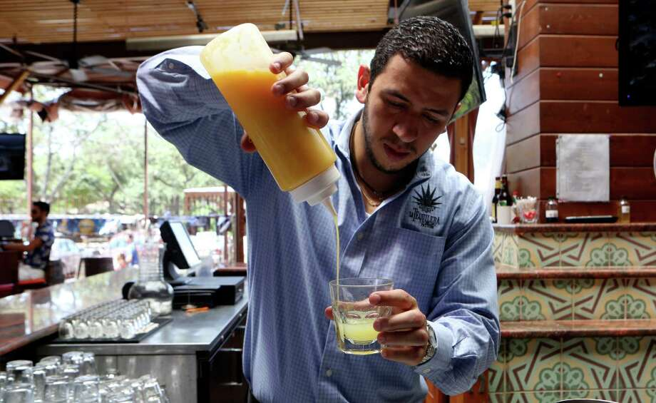 Fernando Echeverri, manager at La Tequilera del Patrón demonstrates how to make a margarita. The margarita at La Tequilera includes lime juice, orange juice, agave nectar, tequila, and orange liqueur. Photo: Express-News File Photo / SAN ANTONIO EXPRESS-NEWS