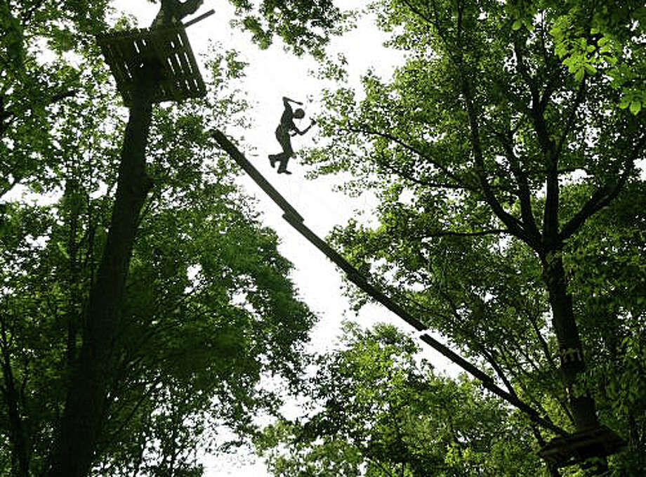 A visitor negotiates the course high in the tree canopy in the Adventure Park at the Discovery Museum in Bridgeport. Photo: File Photo / Westport News