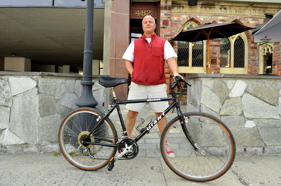 John Robert, with Rippowam Labs, shows off the main bike he takes to his workplace on Summer Street in downtown Stamford, Conn., on Monday, May 11, 2015. From time to time he takes to work a custom-made bike that his friend made. Photo: Jason Rearick / Stamford Advocate