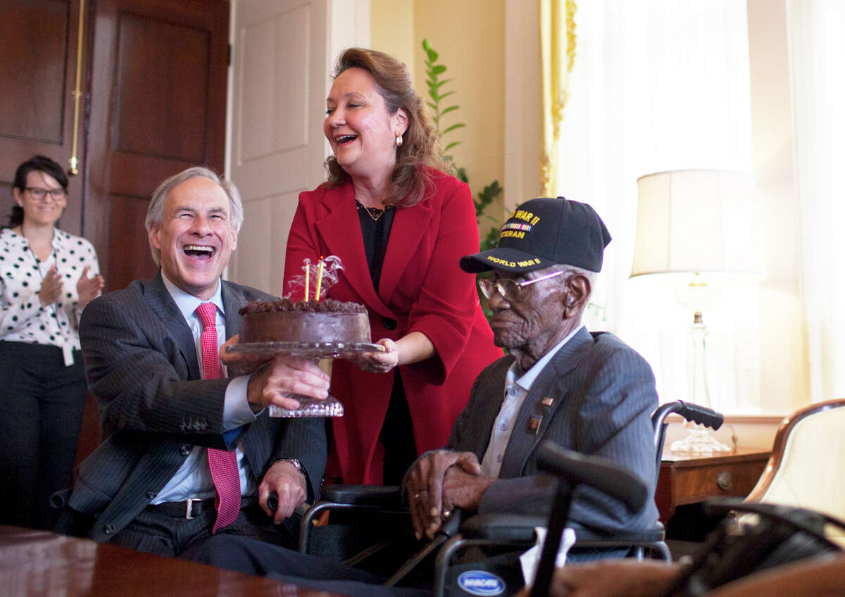 Governor Greg Abbott (left) and First Lady Cecilia Abbott hold up a birthday cake so that Richard Overton (center) can blow out candles during a birthday party for Overton, the oldest living combat veteran from WWII, Monday. May 11, 2015. Governor Greg Abbott and First Lady Cecilia Abbott celebrate Richard Overton's 109th birthday at the Texas Governor's Mansion on Monday, May 11th, 2015. Overton is the oldest living combat veteran from WWII.