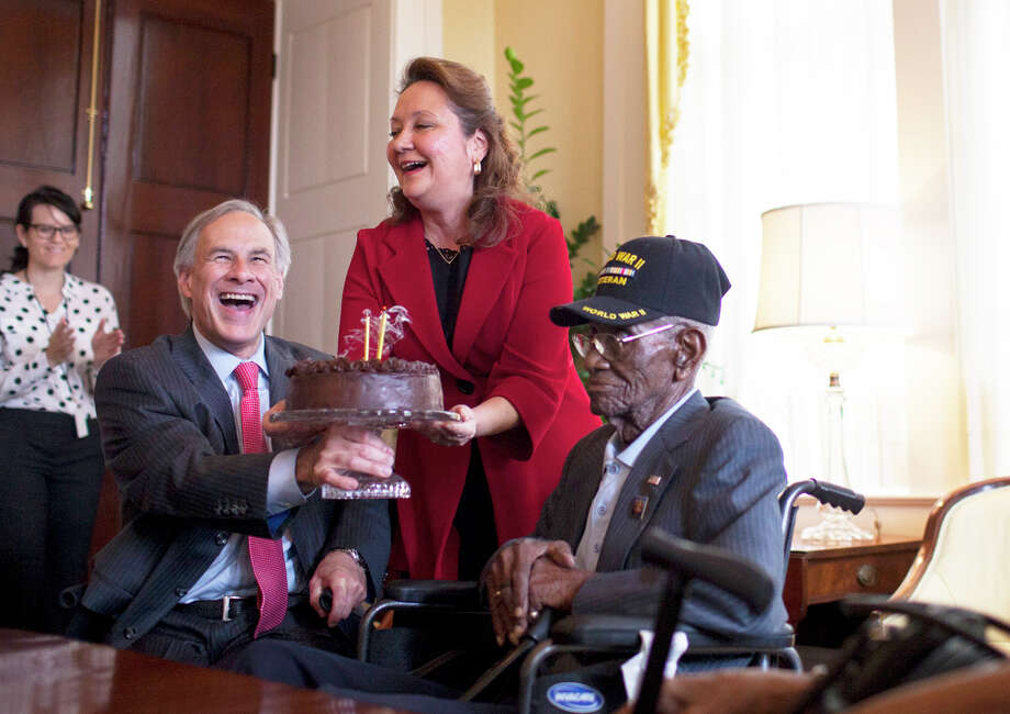 Governor Greg Abbott (left) and First Lady Cecilia Abbott hold up a birthday cake so that Richard Overton (center) can blow out candles during a birthday party for Overton, the oldest living combat veteran from WWII, Monday. May 11, 2015. Governor Greg Abbott and First Lady Cecilia Abbott celebrate Richard Overton's 109th birthday at the Texas Governor's Mansion on Monday, May 11th, 2015. Overton is the oldest living combat veteran from WWII. Photo: Katie Hayes Luke / Katie Hayes Luke