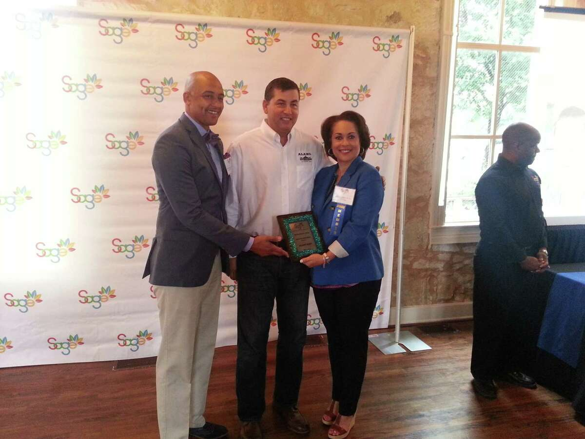 District 2 City Councilman Alan Warrick (left) and SAGE Chair Jelynne Leblanc Burley(right) present Alamo Beer Founder Eugene Simor with the Best Catalytic Investment award at Sunset Station May 6.