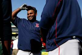 Boston Red Sox' Pablo Sandoval chats with teammates before playing the Oakland Athletics in MLB game at O.co Coliseum in Oakland, Calif., on Monday, May 11, 2015.