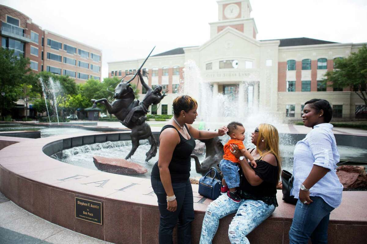 Tyisha Guillory, right, of Sugar Land, takes her baby, Greyson Guillory, for a walk in the Town Center of Sugar Land, along with her  family.
