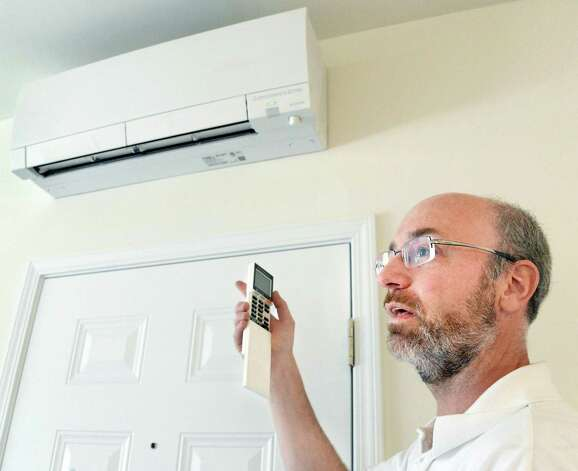 Owner Dave Bruns demonstrates the remote controlled ductless heating and cooling system in an apartment at his netZero village Friday May 8, 2015 in Rotterdam, NY. (John Carl D'Annibale / Times Union) Photo: John Carl D'Annibale / 00031774A