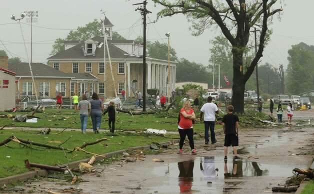 Dozens of Van, Texas, residents walk around the intermediate and elementary schools campuses as they survey the damage from Monday, May 11, 2015 severe weather that moved through the area in the early morning hours. Emergency responders searched through splintered wreckage Monday after a line of tornadoes battered several small communities in Texas and Arkansas, killing at least five people. (AP Photos/Todd Yates) ORG XMIT: TXTY109 Photo: Todd Yates / FR107466 AP