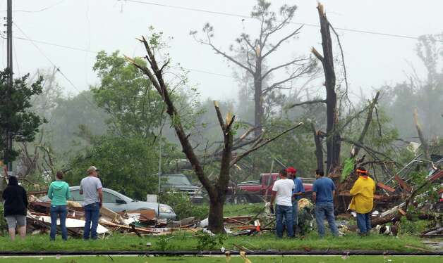 Residents of Van, Texas, residents walk around the intermediate and elementary schools campuses as they survey the damage from Monday, May 11, 2015 severe weather that moved through the area in the early morning hours. Emergency responders searched through splintered wreckage Monday after a line of tornadoes battered several small communities in Texas and Arkansas, killing at least five people. (AP Photos/Todd Yates) ORG XMIT: TXTY111 Photo: Todd Yates / FR107466 AP
