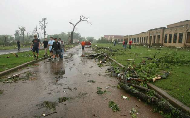Residents of Van, Texas, make their way through storm damage near the towns Intermediate and elementary schools, Monday, May 11, 2015. Emergency responders searched through splintered wreckage Monday after a line of tornadoes battered several small communities in Texas and Arkansas, killing at least five people. (AP Photos/Todd Yates) ORG XMIT: TXTY106 Photo: Todd Yatesa / FR107466 AP