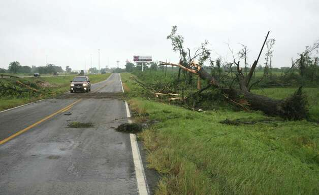 A motorist drives down the access road off of Interstate 20 near Van, Texas, were a tornado cross the interstate before slamming into the town of Van, Monday, May 11, 2015. Emergency responders searched through splintered wreckage Monday after a line of tornadoes battered several small communities in Texas and Arkansas, killing at least five people. (AP Photos/Todd Yates) ORG XMIT: TXTY107 Photo: Todd Yates / FR107466 AP
