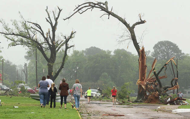 Residents survey damage near an elementary school, caused by severe weather, Monday, May 11, 2015, in Van, Texas. About 30 percent of the community was damaged from the storm late Sunday, according to Chuck Allen, fire marshal and emergency management coordinator for Van Zandt County. (AP Photo/Todd Yates) ORG XMIT: TXTY101 Photo: Todd Yates / FR107466 AP