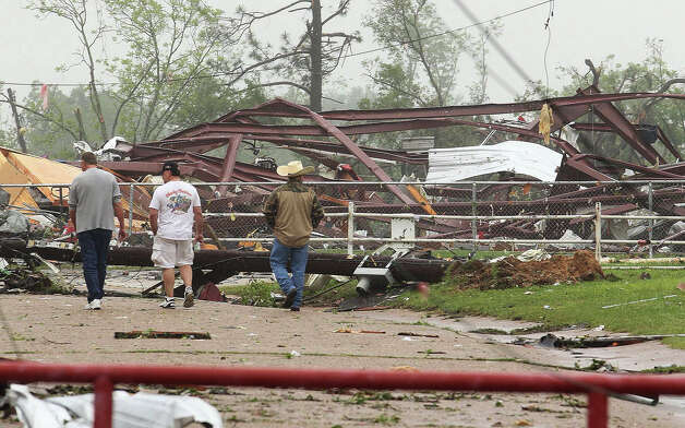 Residents survey damage to an elementary school caused by severe weather, Monday, May 11, 2015, in Van, Texas. About 30 percent of the community was damaged from the storm late Sunday, according to Chuck Allen, fire marshal and emergency management coordinator for Van Zandt County. (AP Photo/Todd Yates) ORG XMIT: TXTY103 Photo: Todd Yates / FR107466 AP