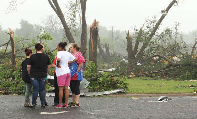 Residents survey damage near an elementary school, caused by severe weather, Monday, May 11, 2015, in Van, Texas. About 30 percent of the community was damaged from the storm late Sunday, according to Chuck Allen, fire marshal and emergency management coordinator for Van Zandt County. (AP Photo/Todd Yates) ORG XMIT: TXTY104 Photo: Todd Yates / FR107466 AP