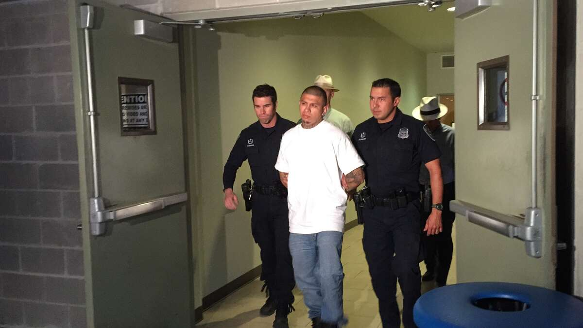 Jeremy Gutierrez, 24, is seen being led away by police on May 11. Gutierrez was wanted in the death of Sylvester Reyes on May 5.
