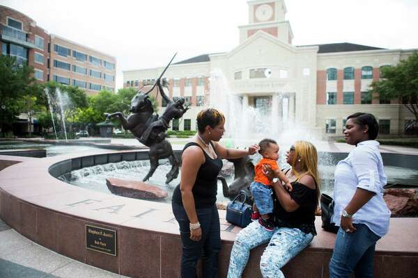 Tyisha Guillory, right, a resident of Sugar Land, takes her baby Greyson Guillory for a walk in the Town Center of Sugar Land, along with her sister Keiljuana Phillips, left, and her mother Cassandra Gentry, center, Friday, May 8, 2015, in Sugar Land.