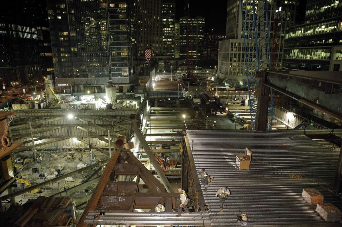 Iron workers bolt together connections between structural steel beams over First Street and place steel decking on top as work continued on the Transbay Terminal on Monday night. Construction workers continued making progress on the structural steel portion of the Transbay Terminal in San Francisco , Calif., on Monday, May 11, 2015. The project reached a milestone as the decks that crossed over First Street were placed over the blocked roadway over the previous weekend and work continued overnight to finish the project.