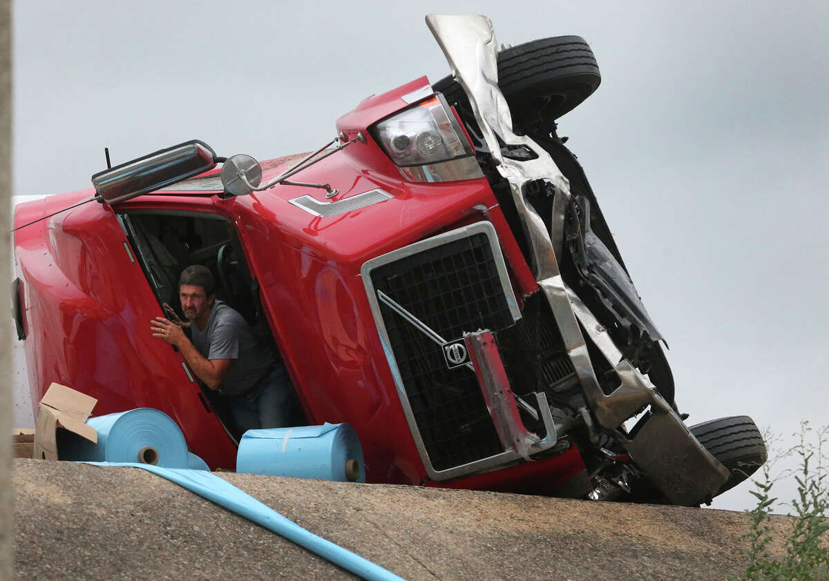 A man who identified himself as the driver of an 18-wheeler tractor trailer rig prepares to emerge from the cab of the truck after it crashed Tuesday May 12, 2015 on Northeast Loop 410 near Austin Highway. The accident happened about 5:30 a.m. and the driver was not injured. The truck was carrying large rolls of blue sheet plastic.Traffic in both directions is slowing down in the area. The driver was looking for items in the cab after it crashed.