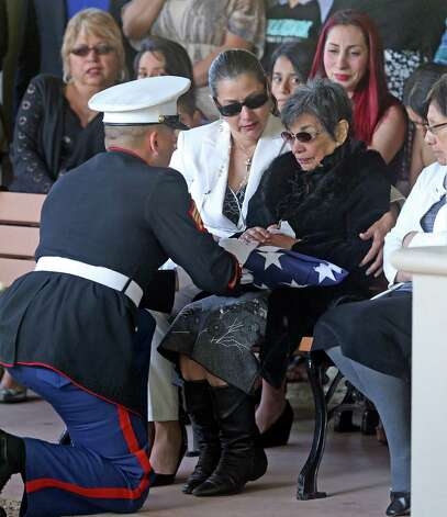Pauline Ayala is given the flag from her husband's coffin as Tony Ayala Sr. is remembered at funeral services at Palm Heights Mortuary and Ft. Sam Houston National Cemetery on April 16, 2014. Photo: TOM REEL