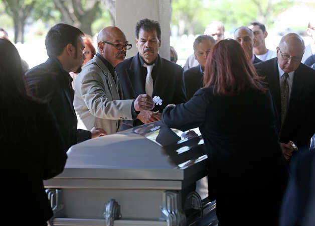 Sam Ayala (center left)  leads family members in paying last respects as Tony Ayala Sr. is remembered at funeral services at Palm Heights Mortuary and Ft. Sam Houston National Cemetery on April 16, 2014. Photo: TOM REEL