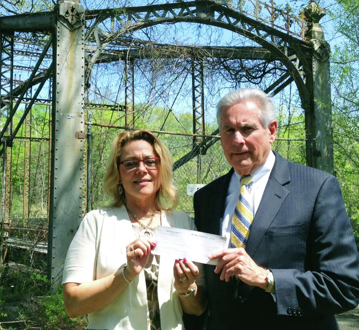 New Milford attorney Lon Moots presents a donation of $1,000 on behalf of the Moots Pellegrini law firm to Mayor Pat Murphy to help fund the restoration project of the Boardman Bridge. May 2015