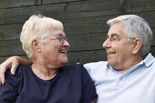 Smiling senior couple relaxing on bench outdoors