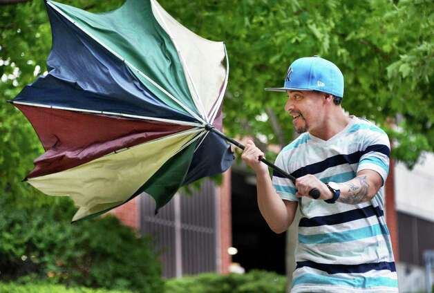 Tony Torres of Schenectady struggles to save his umbrella from high winds and rain as he makes his way along State Street Tuesday May 12, 2015 in Schenectady, NY.  (John Carl D'Annibale / Times Union) Photo: John Carl D'Annibale