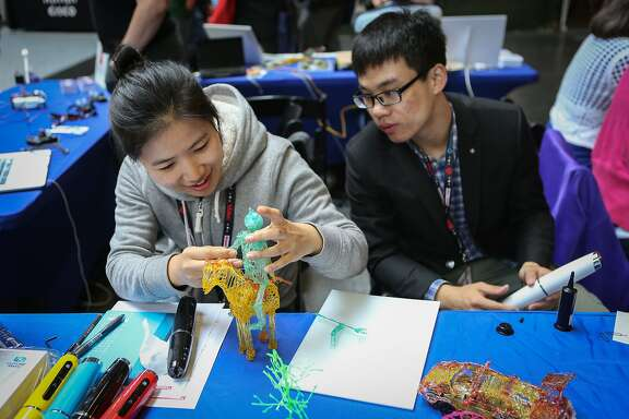 Julia Wang and Charlie Cheng of Future Make demonstrate the creative abilities allowed by the 3D printing pen by Future Make at MakerCon in San Francisco on Tuesday, May 12, 2015.