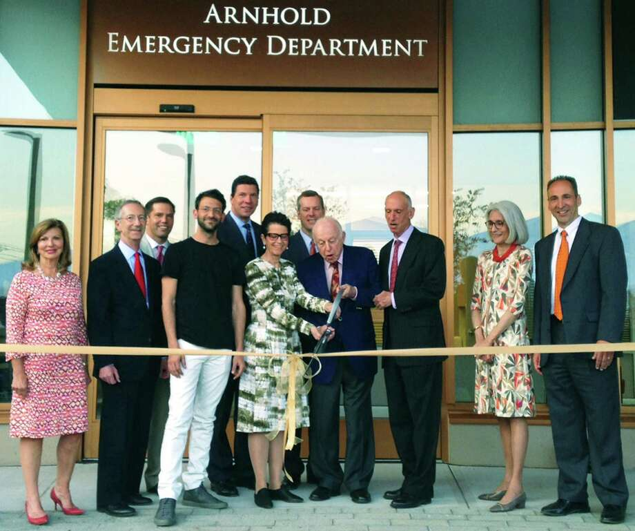 As hundreds look on, the Arnhold family performs the honors Friday, May 8, 2015 at a ribbon-cutting ceremony for the new Arnhold Emergency Department at New Milford Hospital. Sharing the experience are, from left to right, front row, Anthea Disney, Western Connecticut Health Network board of directors; Ervin Shames, chairman of the WCHN board; Paul Arnhold; Jody Arnhold; Henry H. Arnhold; John Arnhold; Deborah Seidel, vice chairwoman of the WCHN Foundation; and Dr. Tom Koobatian, New Milford Hospital's executive director and chief of staff; and, back row, Spencer Houldin, WCHN Board of directors; Dr. John Murphy, WCHN president and CEO; and Daniel DeBarba, president of New Milford and Danbury hospitals. Photo: Norm Cummings / The News-Times