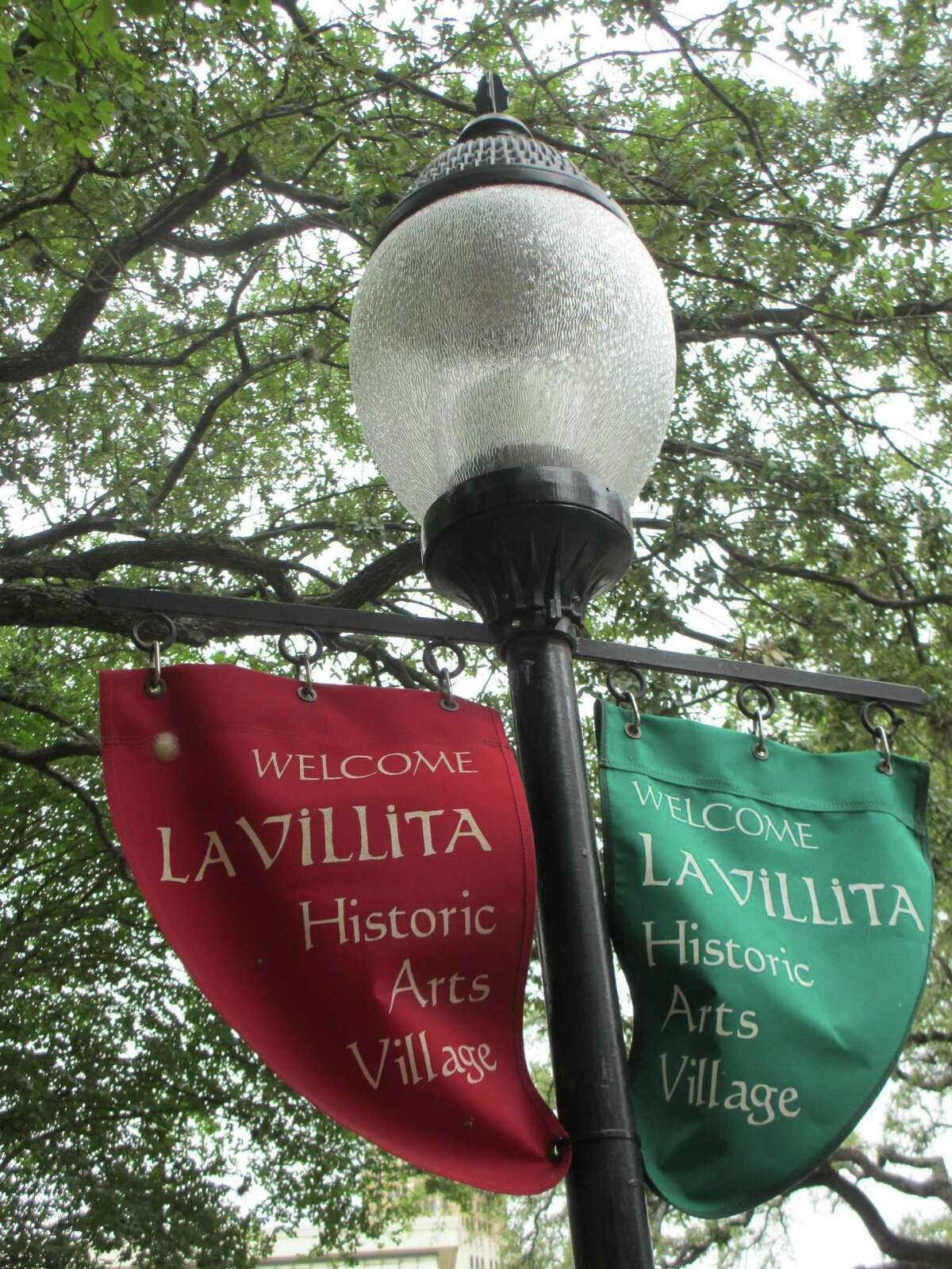 """Red and green """"Welcome to La Villita"""" banners hang on lightpoles through out the historic village in San Antonio."""