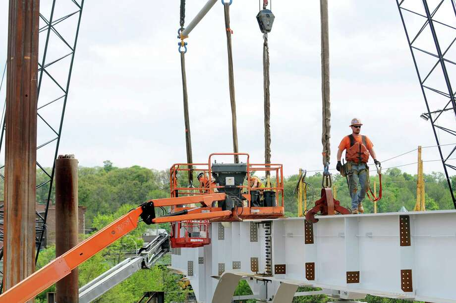 Iron worker Ryan Kelly of D.A. Collins works on the Mohawk Valley Gateway Overlook Pedestrian Bridge on Tuesday, May 12, 2015, in Amsterdam, N.Y. The $16.5 million project will help support the city's economy by connecting the south side's neighborhoods and Erie Canalway Trail with Riverlink Park and downtown Amsterdam on the north side. (Cindy Schultz / Times Union) Photo: Cindy Schultz / 00031781A
