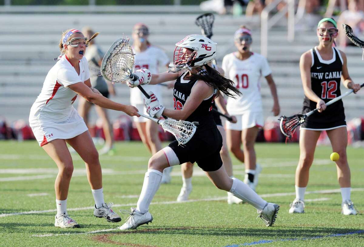Madeline Graves, left, of Greenwich gets her shot past New Canaan goalie Bailey Pilder, center, for a goal during the girls high school lacrosse match between Greenwich High School and New Canaan High School at Greenwich, Conn., Tuesday night, May 12, 2015. Looking on in the background is Romy Villemure (#10) of Greenwich, second from right, and Ellery Baran(#12) of New Canaan, right. New Canaan won the match over Greenwich, 10-9.