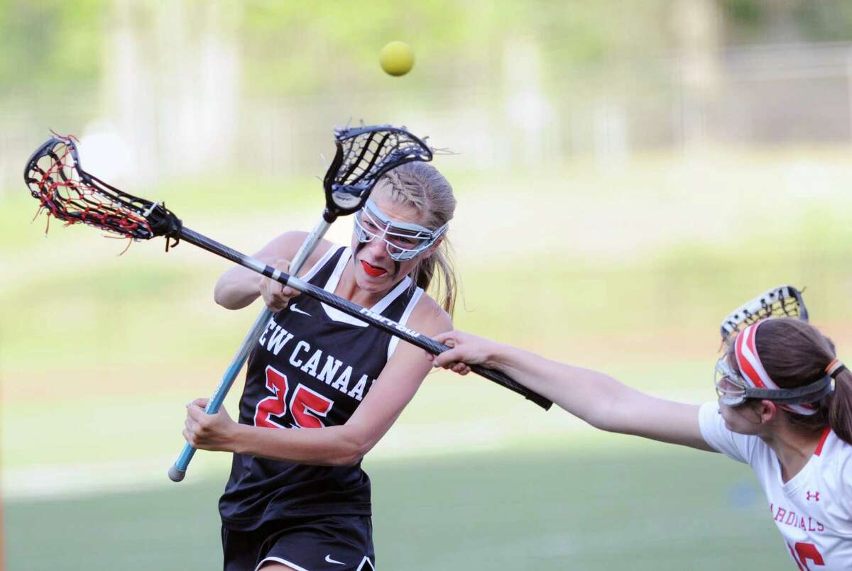 Sloan Caan (#16) of Greenwich, at right, defends a shot by New Canaan's Campbell Armstrong (#25) during the girls high school lacrosse match between Greenwich High School and New Canaan High School at Greenwich, Conn., Tuesday night, May 12, 2015. New Canaan won the match over Greenwich, 10-9.