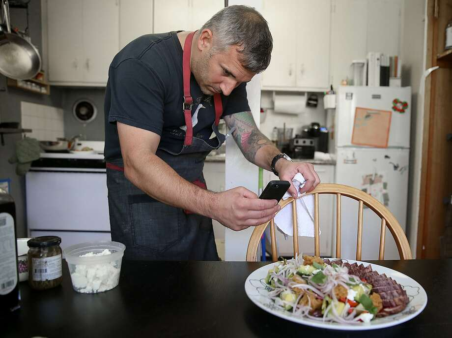Chef David Bazirgan takes a phone picture after making a greek salad with seared tuna at home in San Francisco, California, on Tuesday, May 12, 2015. Photo: Liz Hafalia, The Chronicle