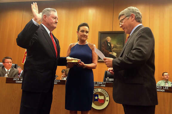 Judge Connie Hickman holds a Bible for her husband, former Precinct 4 Constable Ron Hickman, as he's sworn in as sheriff by Harris County Judge Ed Emmett, right, on Tuesday.