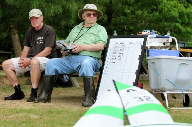 Jeff Warrick of Niskayuna, left, joins Bill Zautner of Glenmont as he remotely controls his sailboat in a regatta on Tuesday, May 12, 2015, at The Crossings in Colonie, N.Y. The Capital Area Model Boat Assoc. meets every Tuesday and Thursday afternoon though mid-October to compete with their boats on the pond. (Cindy Schultz / Times Union) Photo: Cindy Schultz