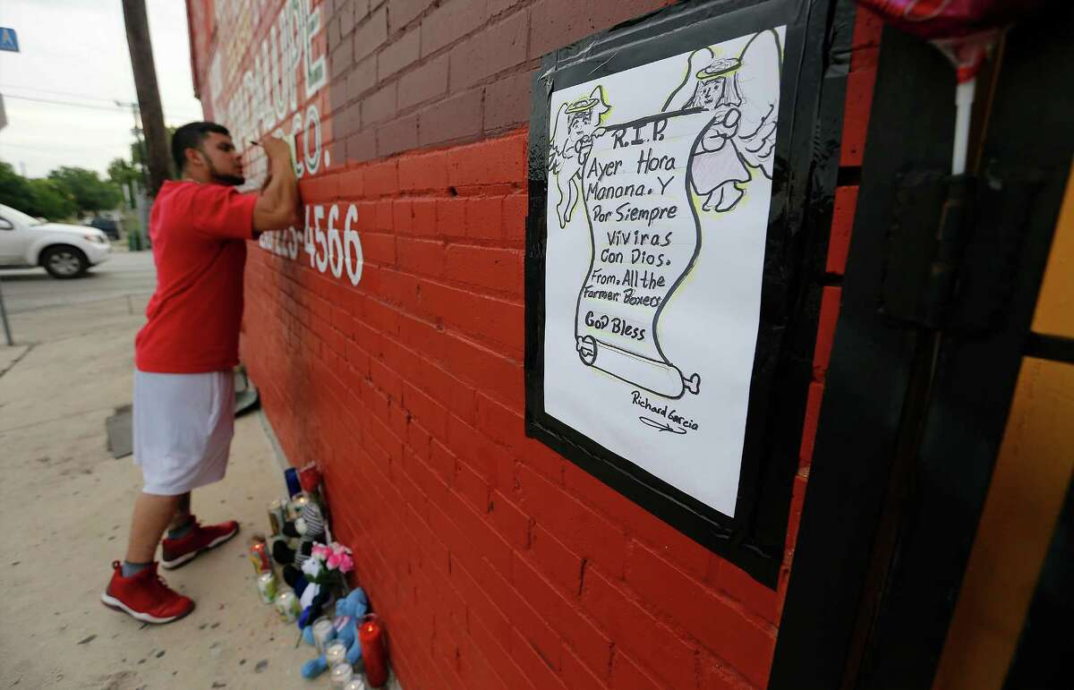"""Reynaldo Mora, Jr. signs a card as he gathers with others to remember local boxing legend Tony Ayala, Jr. at Zarzamora Street Gym on Tuesday, May 12, 2015. News spread of Ayala's passing throughout the regulars like Mora who trained at the gym that Ayala and his father, Tony Ayala, Sr., started in the 1980s. The 52-year-old former boxer was found deceased in the gym. The sign on the right is loosely translated as saying, """"Yesterday, Today and Tomorrow. You will live forever with God."""""""
