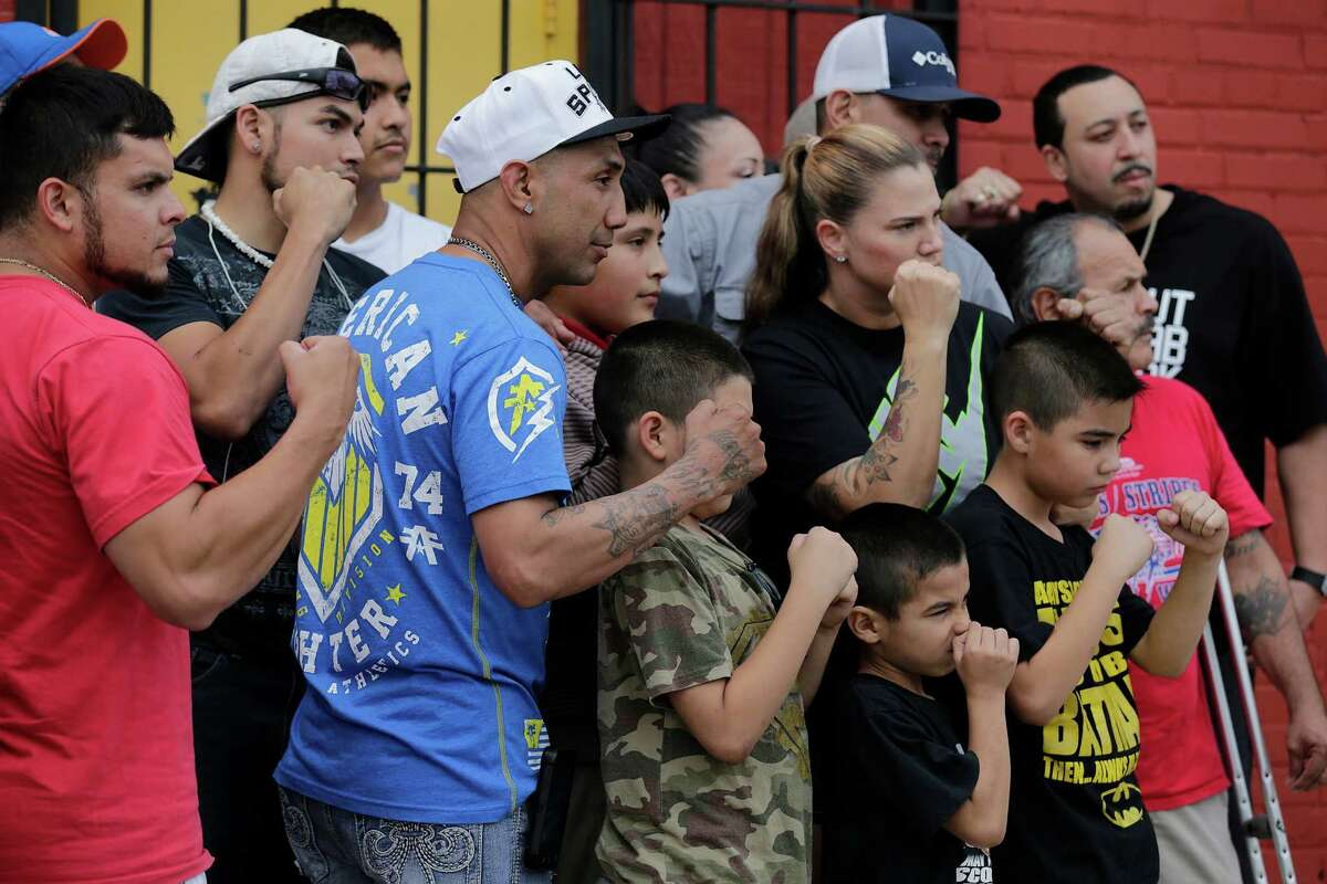 Former bantamweight champion John Michael Johnson (wearing a blue shirt) joins others in a photo to remember local boxing legend Tony Ayala, Jr. at Zarzamora Street Gym on Tuesday, May 12, 2015. News spread of Ayala's death throughout the regulars who trained at the gym that Ayala and his father, Tony Ayala, Sr., started in the 1980s. The 52-year-old former boxer was found deceased in the gym. Johnson said he will try to keep the gym open.